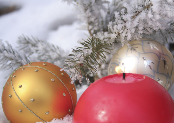 Weihnachtskugeln und Kerze im schnee