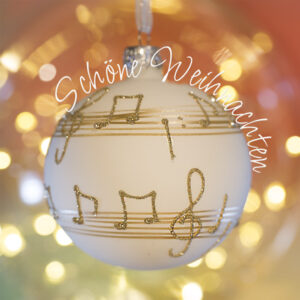 """Christbaumkugel mit Notentext, Lichter im Hintergrund und Text """"Schöne Weihnachten"""""""