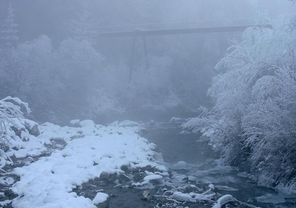Brücke im Winter über einem Bachbett mit Schnee