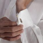Hochzeit Barbara und Tobias, Bräutigam steckt sich die Manschettenknöpfe an
