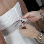 Hochzeit Barbara und Tobias, Trauzeugin hilft der Braut beim anziehen
