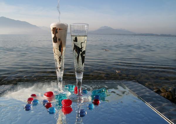 Zwei Champagnergläser auf Spiegel im Zugersee