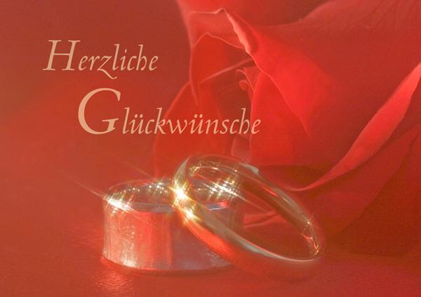 """Eheringe, im Hintergrund rote Rose, Text """"Herzliche Glückwünsche"""""""
