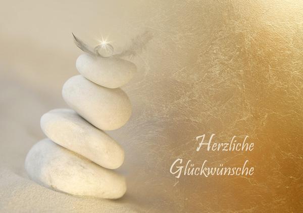 """Turm aus vier hellen Steinen mit Feder und Stern, Text """"Herzliche Glückwünsche"""""""