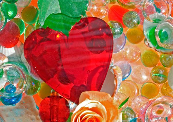 Rotes Glasherz mit farbigen Glassteinen im Wasser